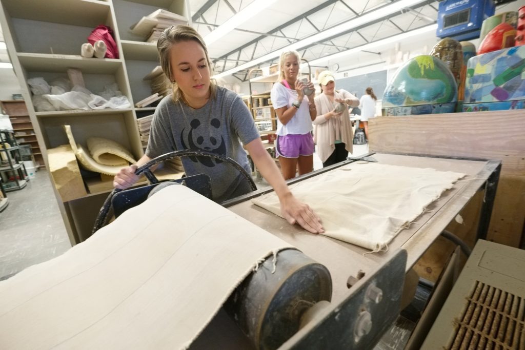 Ellen Salaun uses a press to roll her ball of clay into a flat slab as her classmates await their turn to do the same. Photo by Robert Jordan/Ole Miss Communications